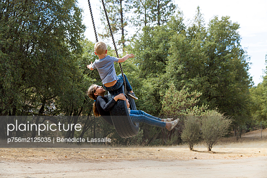 Siblings have fun in a tire swing - p756m2125035 by Bénédicte Lassalle