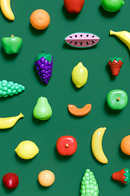 Directly above shot of various fruit toys on green background - p1094m1467615 by Patrick Strattner