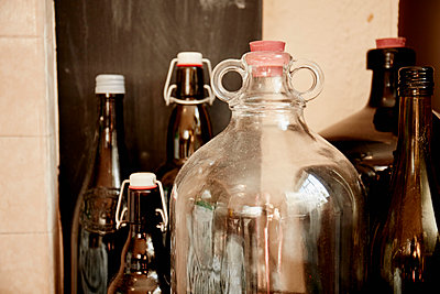 A shelf of bottles and jars, one large double handled jar with a stopper and bottles with lids.  - p1100m1080195f by Mint Images