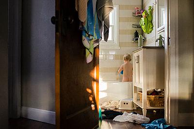 Rear view of naked boy standing in bathtub seen through doorway at home - p1166m1473751 by Cavan Images
