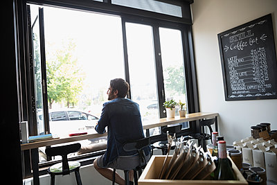 Pensive man sitting at window in cafe - p1192m1490847 by Hero Images