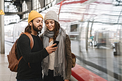 Young couple using smartphone at the station platform as the train comes in, Berlin, Germany - p300m2155177 von Hernandez and Sorokina