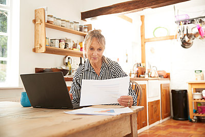 Active senior woman looking at paper using laptop sitting in kitchen at home - p300m2227138 by Pete Muller