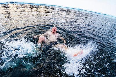 Man swimming in freezing cold lake - p322m938866 von Simo Vunneli