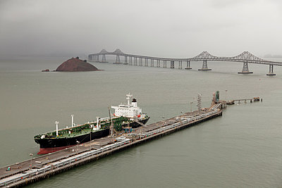 Oil tanker offloading in urban dock - p555m1420391 by Tom Paiva Photography