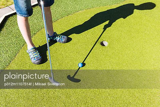 Boy playing mini golf