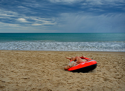Man asleep in rubber raft on beach - p1125m2013965 by jonlove