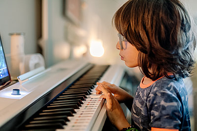 Kid looking at screen while playing on a smart piano keyword - p1166m2095850 by Cavan Images