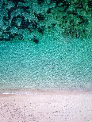 Indonesia, Bali, Melasti, Aerial view of Karma Kandara beach, woman swimming - p300m2042545 by Konstantin Trubavin