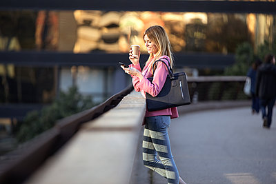 Young businesswoman using smartphone and holding coffee to go - p300m2114632 by Josep Suria