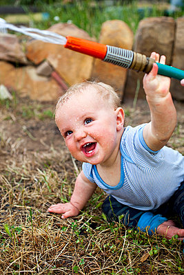 A laughing baby boy holding a garden hose - p301m799536f by Tobias Titz
