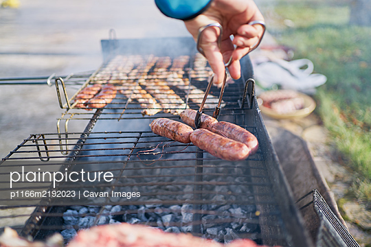 preparation of barbecue on bacon and sausage grill - p1166m2192023 by Cavan Images