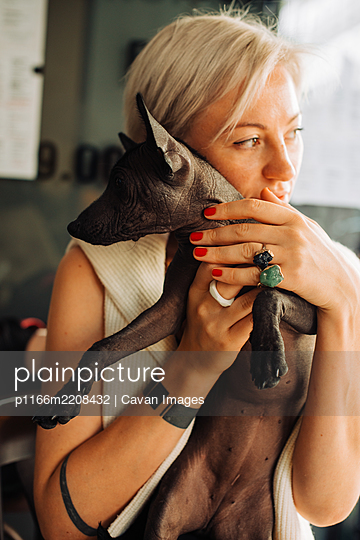 Blond Caucasian woman and small black dog on her lap - p1166m2208432 by Cavan Images