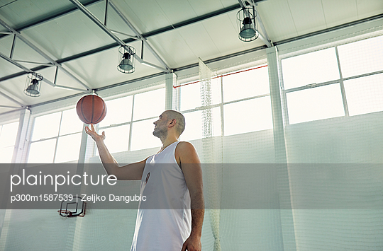 Man playing with basketball, indoor - p300m1587539 von Zeljko Dangubic