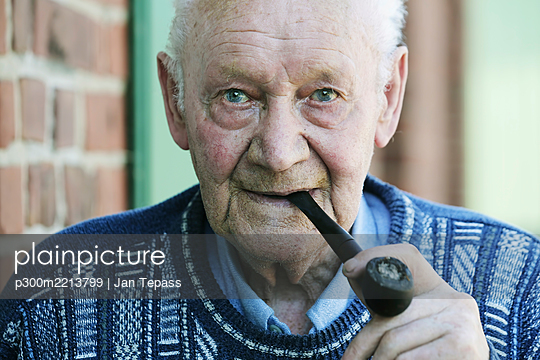 Germany, Portrait of senior man holding pipe, close up - p300m2213799 by Jan Tepass