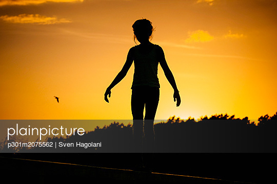 Silhouette woman standing against sunset sky - p301m2075562 by Sven Hagolani