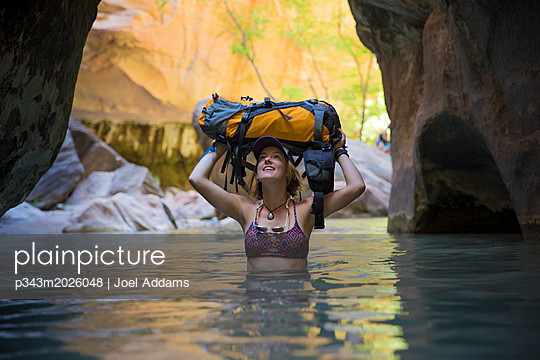 A woman explores the Narrows in Zion National Park, Utah. - p343m2026048 by Joel Addams