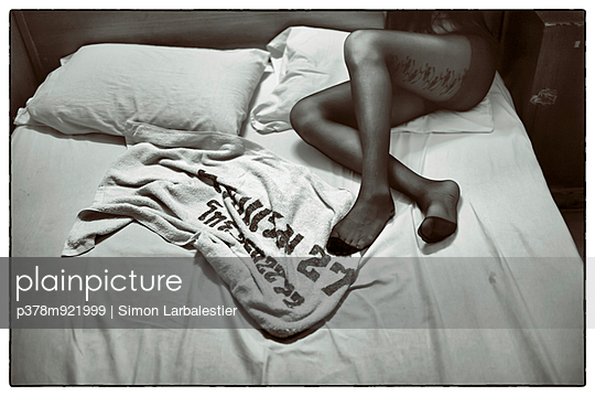Womans legs on bed - p378m921999 by Simon Larbalestier