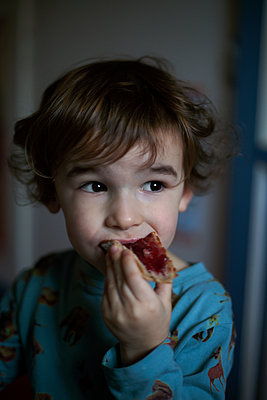 Young boy eating bread and jam - p1028m2100732 by Jean Marmeisse