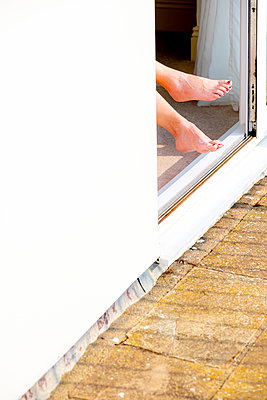 Bare fenale feet with red painted toe nails sticking out of a doorway in the sun. - p1057m2206390 by Stephen Shepherd