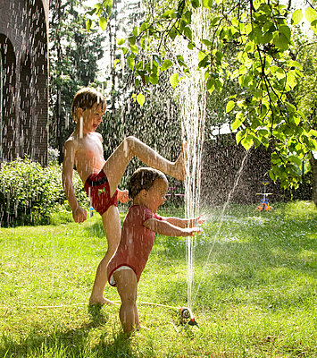 Children playing under the sprinkler - p1231m1059788 by Iris Loonen