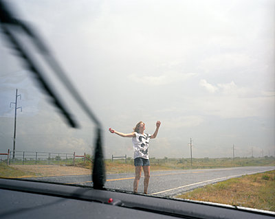 girl dancing in the rain on the road - p1610m2181503 by myriam tirler