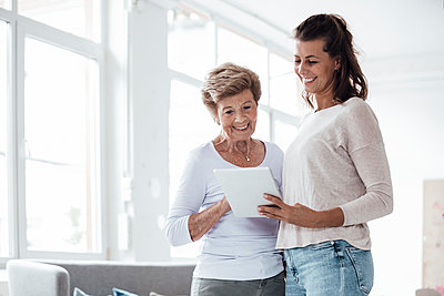 Smiling grandmother and young woman looking at digital tablet - p300m2274883 by Gustafsson
