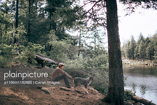 Side view of man with Australian Shepherd by lake in forest - p1166m1182885 by Cavan Images