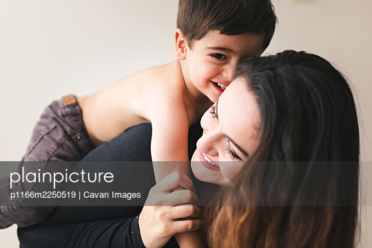 Mom giving young son a piggy back ride. - p1166m2250519 by Cavan Images
