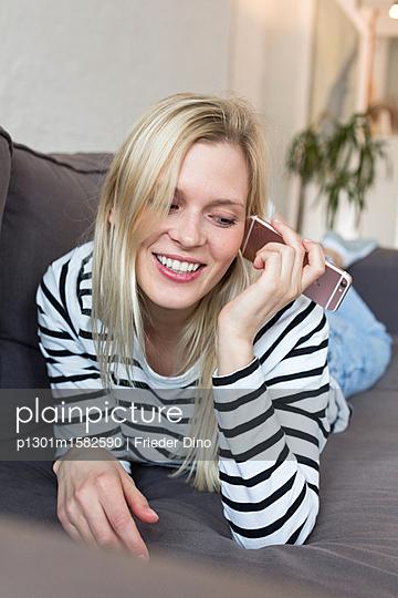 Junge Frau mit Smartphone auf dem Sofa - p1301m1582590 von Delia Baum