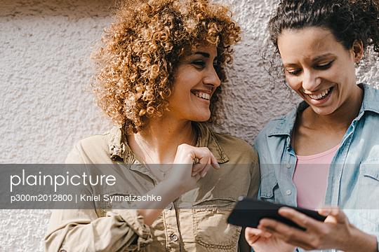 Best friends in the city using smartphone - p300m2012800 von Kniel Synnatzschke