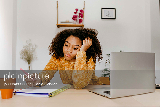 Young woman working while sitting with head in hands at home office - p300m2256662 by Tania Cervián