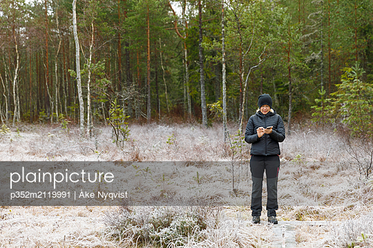 Mature woman standing in front of a forest - p352m2119991 by Åke Nyqvist