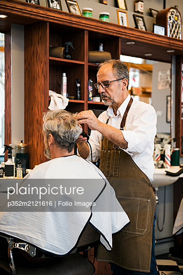 Barber cutting customer´s hair - p352m2121616 by Folio Images