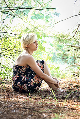 Sad woman with blond hair sitting in the forest - p1019m1425484 by Stephen Carroll