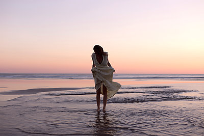 Woman holding dress while standing on shore at beach against clear sky during sunset - p1166m1544478 by Cavan Social