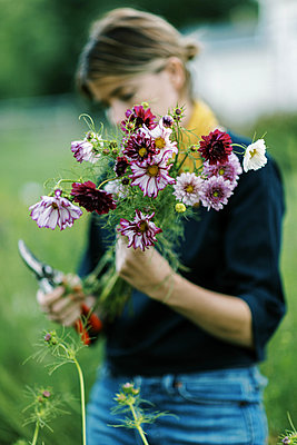 Millennial woman working at her flower farm making bouquets - p1166m2207822 by Cavan Images