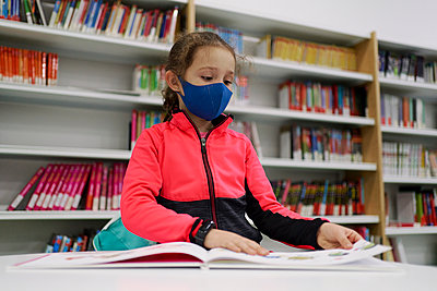 Little girl wearing a medical mask and reading a book in a libra - p1166m2232512 by Cavan Images