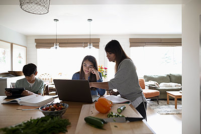 Mother cooking and helping tween daughter at laptop in kitchen - p1192m2000292 by Hero Images