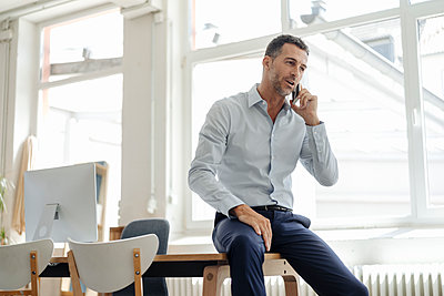 Businessman in office talking on cell phone - p300m1499651 by Kniel Synnatzschke