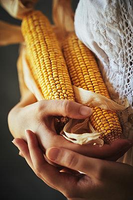 Frau hält Maiskolben - p968m2020219 von roberto pastrovicchio