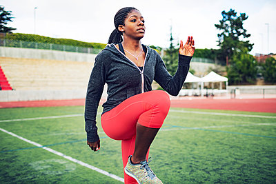 Determined female athlete exercising on field - p1166m1086163f by John Trice
