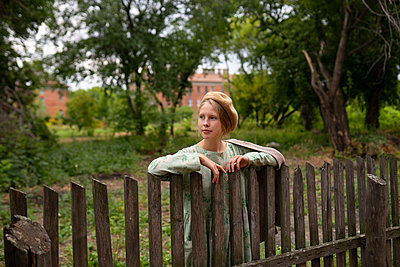 young woman at her garden fence - p1646m2260612 by Slava Chistyakov