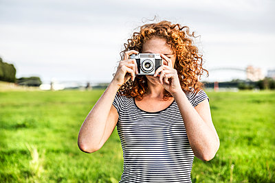 Young woman on a meadow taking picture of viewer with camera - p300m2070517 by Jo Kirchherr