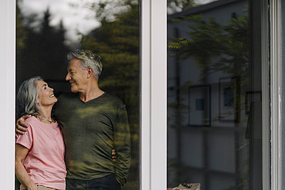 Happy senior couple behind windowpane of their home - p300m2154990 by Gustafsson