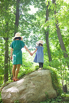 Mother And Girl On Rock In Forest - p463m1066036 by Yo Oura