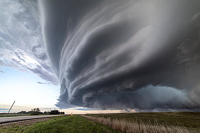 Sculpted super-cell, a mesocyclone weather formation thunderstorm clouds, drifting majestically across the Nebraska sand hills. - p924m2196790 by Jessica Moore