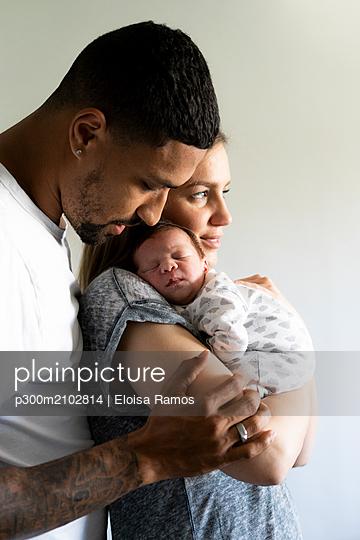 Parents cuddling with sleeping newborn baby - p300m2102814 by Eloisa Ramos
