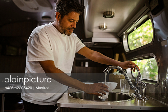 Man filling drinking water through faucet in camper trailer - p426m2205420 by Maskot