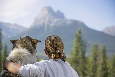 Rear view of teenage girl with dog looking at view while sitting in Banff National Park - p1166m2025237 by Cavan Social